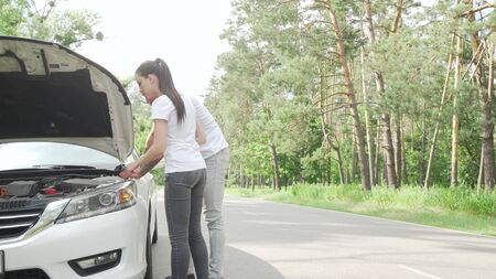 Young couple looking under the hood of their broken car on countryside road. African man and his girlfriend waiting for tow truck service or mechanic after their car broke during road trip