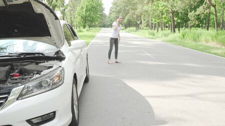 Female driver calling tow truck service after her car broke on countryside road. Selective focus on broken car with open hood, woman calling tow truck service on background Stock fotó