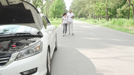 Couple waiting for tow truck service on countryside road. Selective focus on broken auto with open hood, African man and his girlfriend waiting for help on countryside road