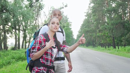 Beautiful multiracial couple hitchhiking on countryside road. Lovely couple with backpacks enjoying travelling together, catching a ride on a road. Travel, tourism concept Archivio Fotografico