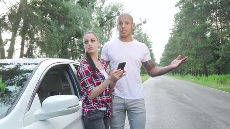 Young couple using smart phone while travelling by car. Multiracial couple looking for driving direction, standing near car on road trip on countryside road. Navigation concept Banque d'images - 130729828