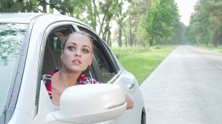 Young woman sitting in her car looking around on countryside road. Beautiful female driver travelling by car in countryside, copy space. Destinations, navigation concept Archivio Fotografico