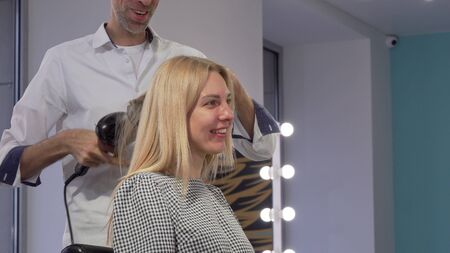 Lovely young woman smiling, while getting her hair styled by hairdresser. Cheerful female client enjoying getting new hairdo by professional hair stylist. Beauty, femininity concept