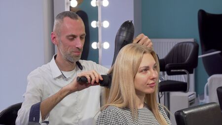 Mature male hairdresser blow drying hair of a female client at the salon. Cheerful aged stylist enjoying working, styling hair of a young lovely woman. Profession, occupation concept Archivio Fotografico