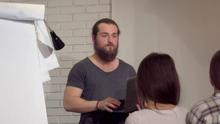 Young bearded businessman leading a meeting with colleagues at the office. Cheerful male entrepreneur using his laptop, talking to the audience in conference room