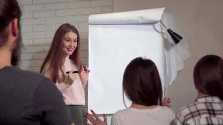 Young businesswoman drawing on flipchart, leading business conference. Attractive female entrepreneur having business presentation with her coworkers Archivio Fotografico