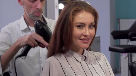 Gorgeous woman smiling to the camera while getting her hair blow dried. Cropped shot of a professional hairdresser working, using blow dryer while styling hair of female client
