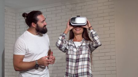 Handsome bearded man watching his girlfriend using virtual reality glasses. Beautiful woman wearing 3d vr headset with her friend standing by. Friendship, science concept Archivio Fotografico