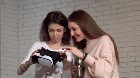 Two lovely female friends using 3d virtual reality goggles together. Beautiful woman wearing vr headset, talking to her friend. Friendship, technology, leisure concept Archivio Fotografico