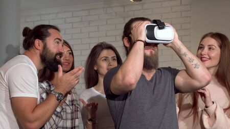 Bearded man using virtual reality glasses with his friends. Group of cheerful people trying 3d vr goggles for the first time. Young man enjoying using vr headset. Friendship, science concept
