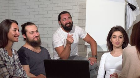 Business team applauding during meeting at the office. Handsome bearded mature businessman and his employees taking during brainstorming session, applauding to a colleague