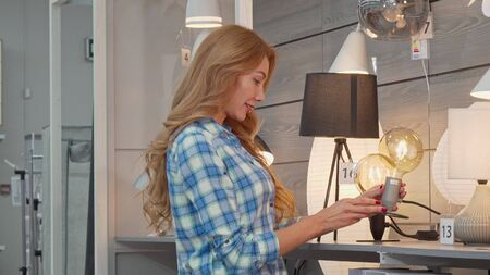 Beautiful woman shopping for lighting for her apartment at furniture store. Gorgeous long haired female customer choosing lamps at home goods shop. Consumerism, home interior concept