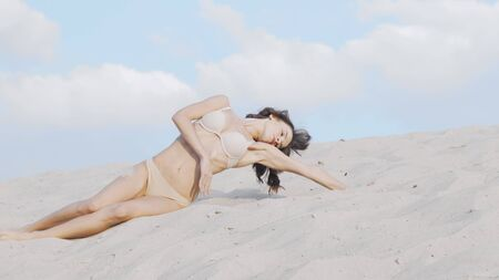 Gorgeous woman in beige bikini posing sensually on sand in the desert. Stunning fit female dancer moving gracefully, sitting on the sand. Seduction, flexibility concept