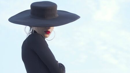 Elegant red lipped woman dressed in black turning to the camera. Mysterious beautiful woman with red lips wearing big black hat, posing gracefully outdoors Archivio Fotografico