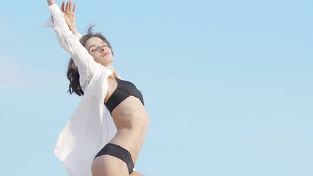 Beautiful flexible woman dancing outdoors in black bikini and white shirt. Stunning young female dancer practicing her dance under blue sky. Nature, vitality concept