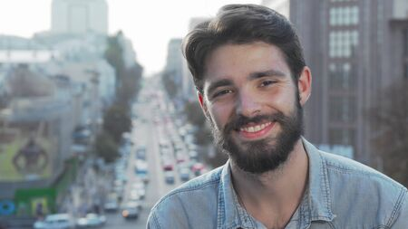 Young bearded man smiling to the camera with city on background. Handsome male hipster relaxing outdoors, looking to the camera joyfully. Youth, lifestyle concept
