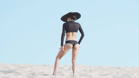 Rear view shot of a fit athletic female dancer performing outdoors on sand. Elegant slim woman wearing black outfit and hat, dancing in the desert. Dance, expressive concept