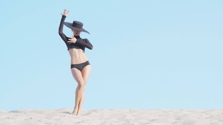 Stunning elegant woman in big black hat dancing on sand. Mysterious female dancer practicing her moves in the desert outdoors, copy space. Elegance, grace, performance concept