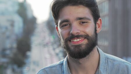 Cheerful handsome bearded man smiling to the camera. Cropped portrait of a charming young man looking to the camera with a smile, busy city streets on background
