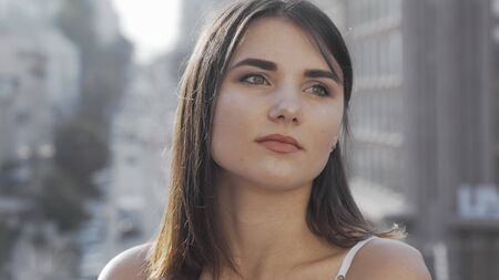 Beautiful woman looking away while waiting someone to meet in the city. Attractive young female looking around on city background. Charming female cropped portrait