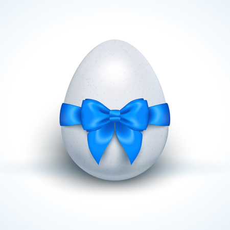 its a boy: Egg with blue ribbon bow isolated on white