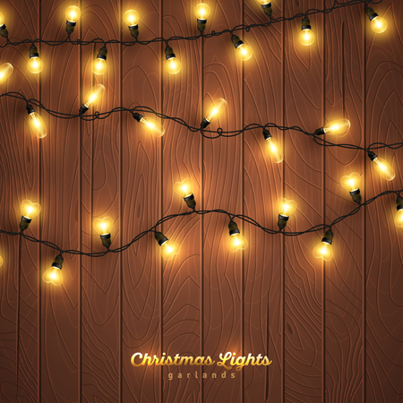 Yellow christmas lights on wooden background Vectores