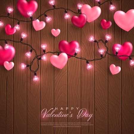 Happy Saint Valentines day card with pink hearts and light garland on brown wood background.
