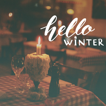 glass wine: Hello winter text overlay on toned photo of restaurant with candle and wine glass.