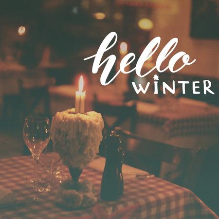 copa de vino: Hola superposición de texto de invierno en tonos foto de restaurante con velas y copa de vino.