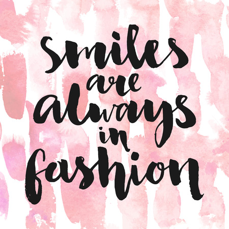 fashion design: Smiles are always in fashion. Inspirational quote handwritten with black ink and brush, custom lettering for posters, t-shirts and cards. Vector calligraphy on pink watercolor strokes background.