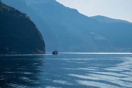 작은 우주선 큰 mountais와 푸른 물에 항해. 노르웨이 풍경, 협만 크루즈. 스톡 콘텐츠