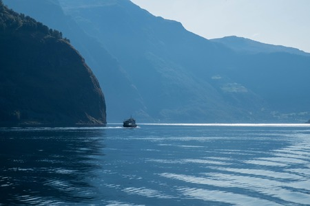 Small ship sails in blue water with large mountais. Norway landscape, fjord cruise.