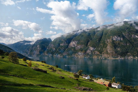 Top view of Norway fjord coast with small village. Green field and tiny wooden houses on the bank of Aurlandsfjord. Ilyllic peaceful landscape at summer Фото со стока - 86869229