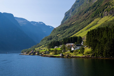 Small Norway village on the fjord bank. Peaceful scandinavian landscape with mountains. View from the water. Фото со стока