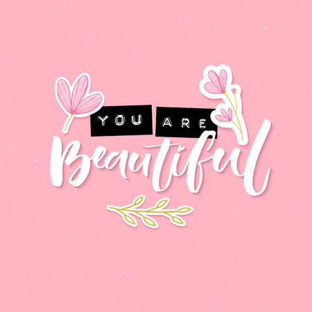 You are beautiful. Inspirational quote with embossed metal letters and modern brush calligraphy decorated with hand drawn flowers on pink background. Trendy collage for social media and apparel.