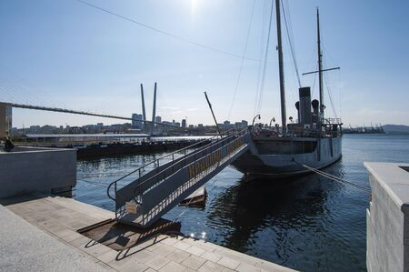 embankment of the city of Vladivostok with a sail - motor ship at the pier -red pennant Imagens