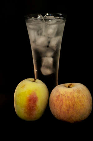 frozen apples and glasses with ice on a black background