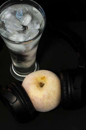 glass with ice and frozen apple in headphones close-up on a black background