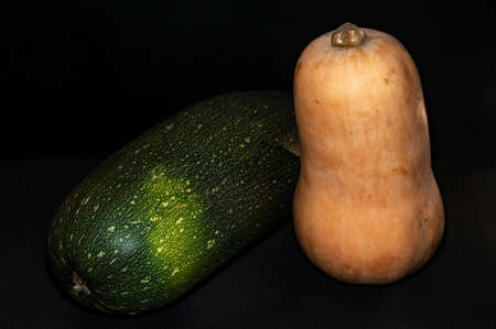 horizontal photo of zucchini and pear-shaped pumpkin close-up on black background Stock fotó