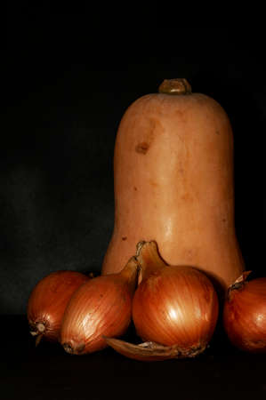 vertical photo of a pear-shaped pumpkin and onion close-up on a black background
