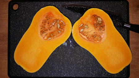 art photo of a cut pear-shaped pumpkin with seeds on a black board