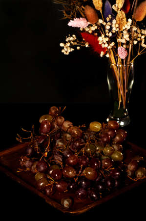 art photo of grapes on a wooden plate with a bouquet of dried flowers Stock fotó