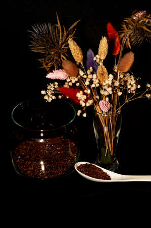 art photo of flax seeds in a jar and a spoon with a bouquet of dried flowers on a black background