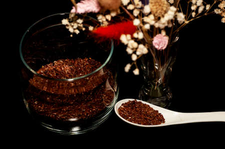 vertical art photo of flax seeds in a jar and spoon with a bouquet of dried flowers on a black background Stock fotó