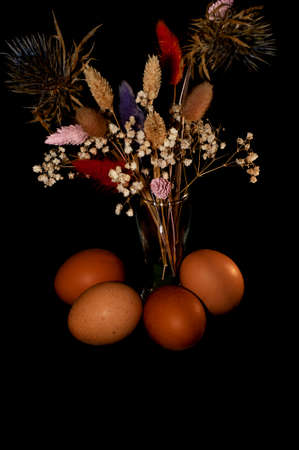 vertical art photo of chicken eggs with a bouquet of dried flowers on a black background Stock fotó