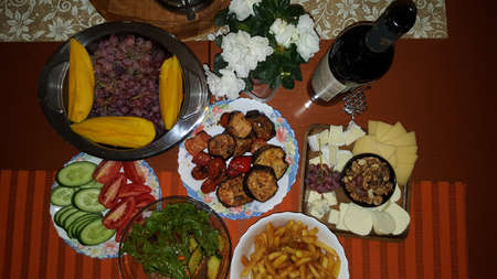 cheese plate grapes and mango grilled vegetables cucumbers and tomatoes and a bottle of wine Stock fotó