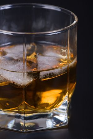 bar ware: Whisky in a glass with ice against a dark background Stock Photo