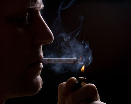 The man smokes a cigarette against a dark background Foto de archivo