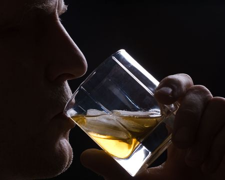 The man drinks whisky with ice from a glass against a dark background