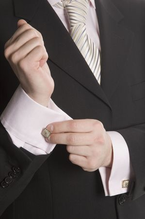 corrects: The man in a business suit corrects a cuff link Stock Photo